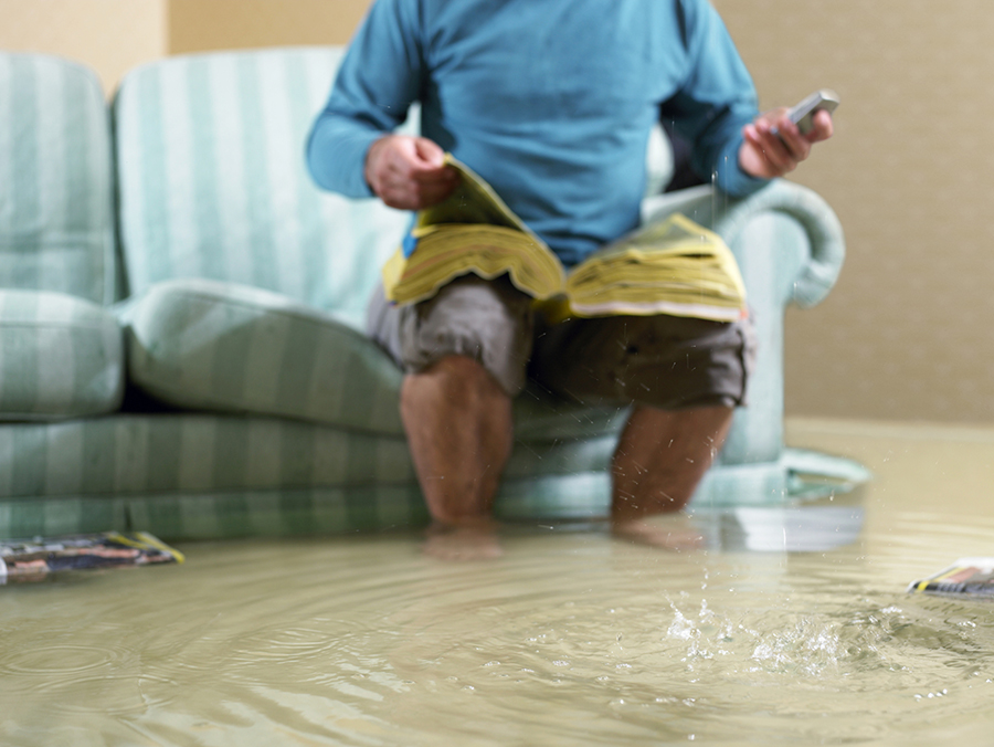 Man sitting in flooded living room using phone, low section